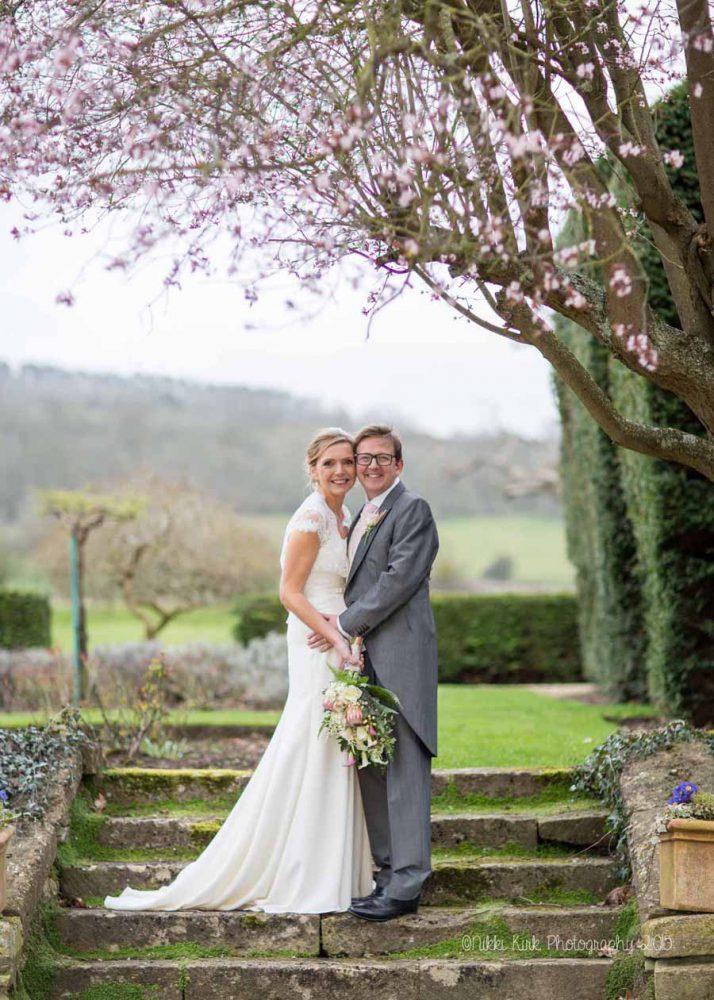 The-Greenway-Hotel-Shurdington-wedding-photographer-Nikki-Kirk-Photography-Cheltenham-Cotswolds-wedding-bride-and-groom-under-a-pink-blossom-tree.jpg